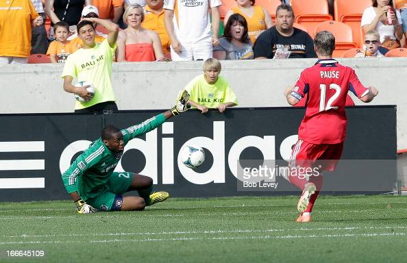 Sean Johnson of the Chicago Fire makes a save in the second half against the Houston Dynamo as Logan Pause looks to clear a rebound at BBVA Compass...
