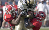 Sean Jones and Tony Taylor of the Georgia Bulldogs tackle Jerod Void of the Purdue Boilermakers on January 1 2004 during the Capital One Bowl at...