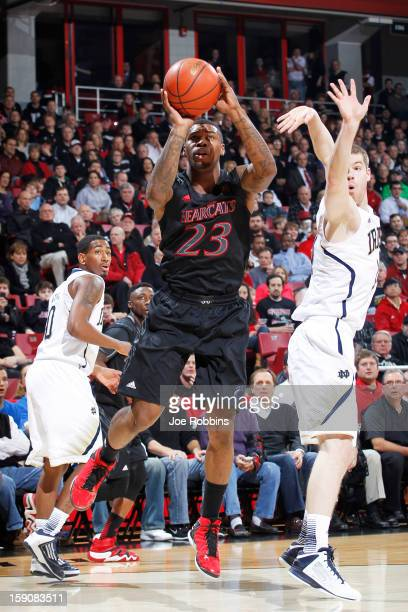 Sean Kilpatrick of the Cincinnati Bearcats shoots the ball against Scott Martin of the Notre Dame Fighting Irish during the game at Fifth Third Arena...