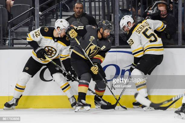 Sean Kuraly and Tim Schaller of the Boston Bruins battle for the puck along the boards with PierreEdouard Bellemare of the Vegas Golden Knights...