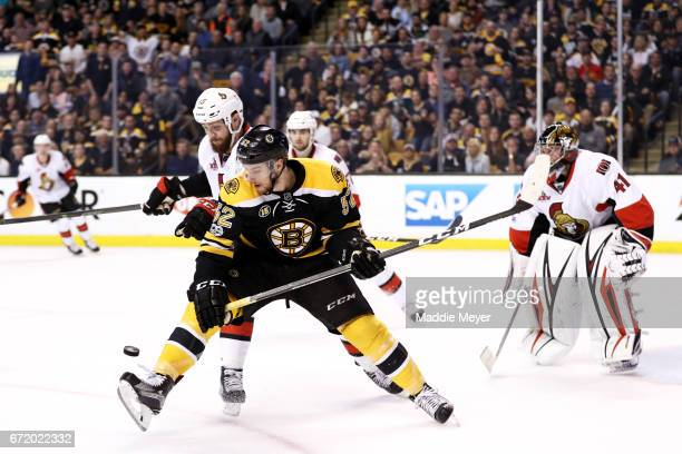 Sean Kuraly of the Boston Bruins and Zack Smith of the Ottawa Senators battle for control of the puck during the third period of Game Six of the...