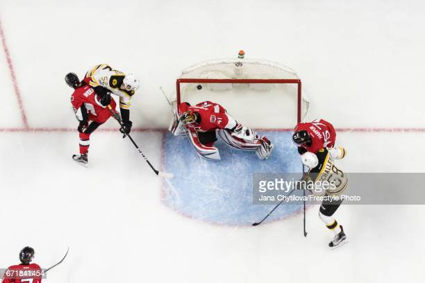 Sean Kuraly of the Boston Bruins buries the puck past Craig Anderson of the Ottawa Senators in the second period as Chris Wideman and Ben Harpur of...