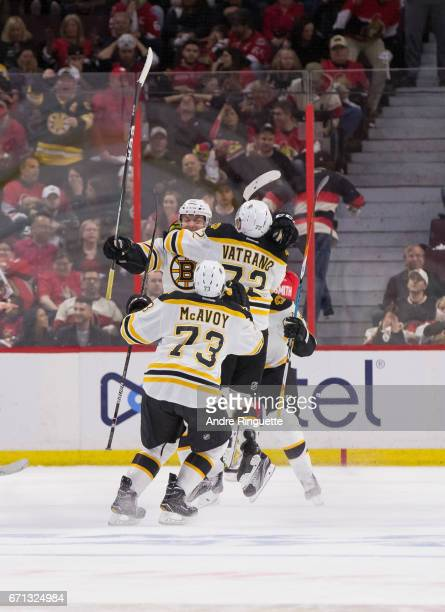 Sean Kuraly of the Boston Bruins celebrates his gamewinning overtime goal against the Ottawa Senators with teammates Charlie McAvoy and Frank Vatrano...