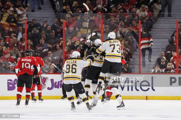 Sean Kuraly of the Boston Bruins celebrates his gamewinning overtime goal against the Ottawa Senators with teammates Kevan Miller Charlie McAvoy and...