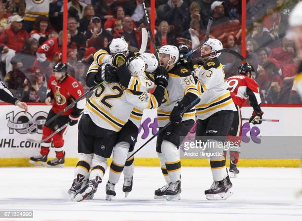 Sean Kuraly of the Boston Bruins celebrates his gamewinning overtime goal against the Ottawa Senators with teammates David Backes Kevan Miller...