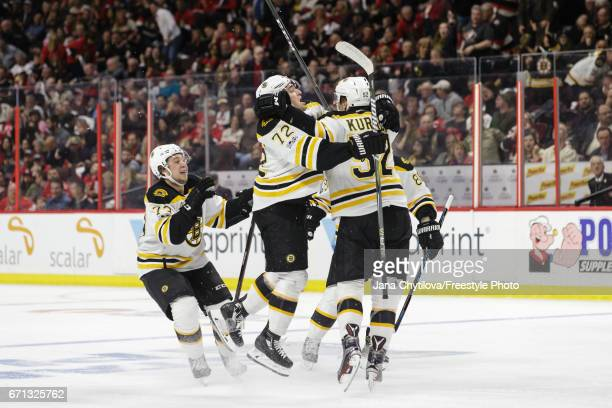 Sean Kuraly of the Boston Bruins celebrates his winning goal in the second overtime period against the Ottawa Senators with teammates Frank Vatrano...
