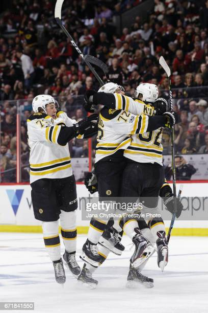 Sean Kuraly of the Boston Bruins celebrates his winning goal in the double overtime period against the Ottawa Senators with teammates Frank Vatrano...