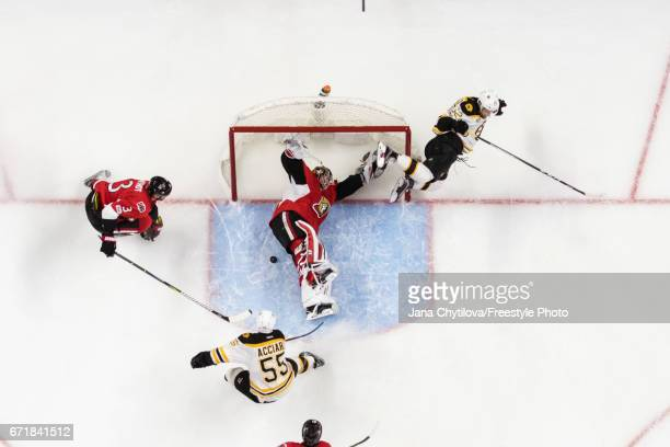 Sean Kuraly of the Boston Bruins flies through the air after colliding with Craig Anderson of the Ottawa Senators as Buddy Robinson of the Boston...