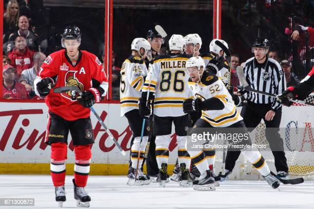 Sean Kuraly of the Boston Bruins skates to the bench to celebrate his second period goal as Kyle Turris of the Ottawa Senators looks on in Game Five...