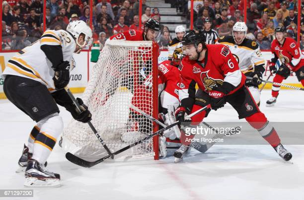 Sean Kuraly of the Boston Bruins slides the puck past Chris Wideman and Craig Anderson of the Ottawa Senators for his second period goal in Game Five...