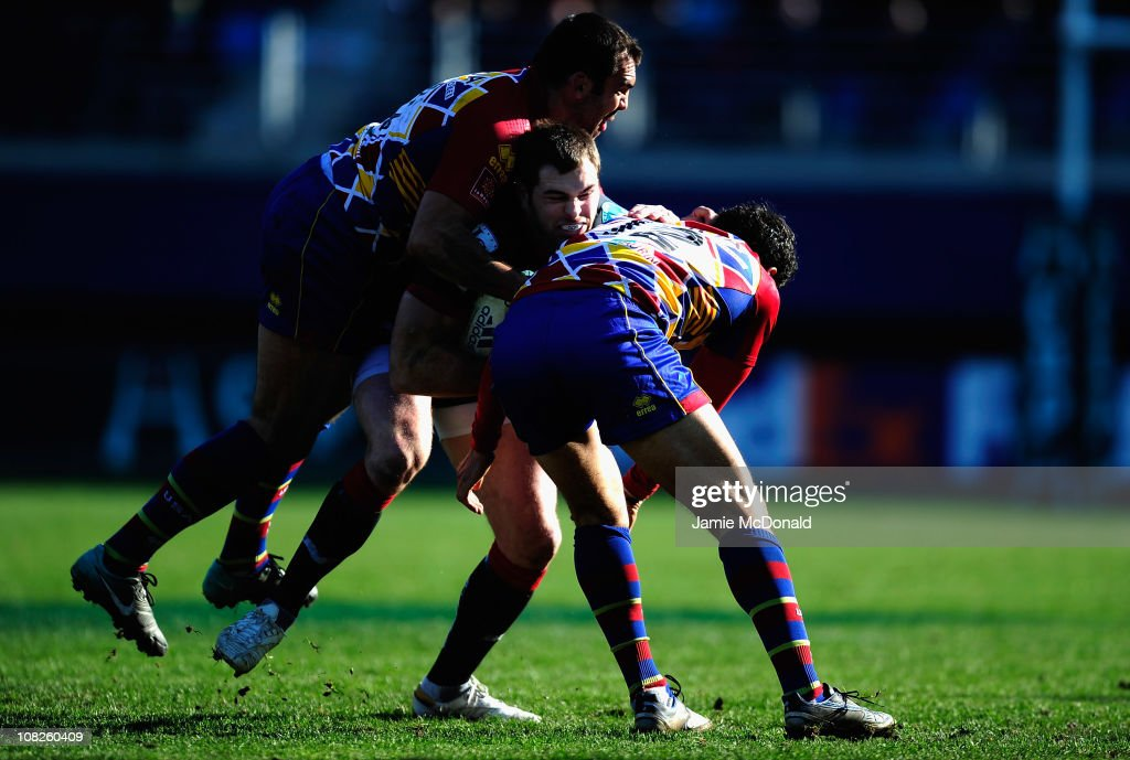 <a gi-track='captionPersonalityLinkClicked' href=/galleries/search?phrase=Sean+Lamont&family=editorial&specificpeople=241325 ng-click='$event.stopPropagation()'>Sean Lamont</a> of Scarlets is tackled by Mermoz Maxime and Mas Nicolas during the Heineken Cup Pool 5 match between Perpignan and Scarlets at the Stade Aime Giral on January 23, 2011 in Perpignan, France.