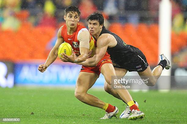 Sean Lemmens of the Suns is tackled by Angus Monfries of the Power during the round 22 AFL match between the Gold Coast Suns and the Port Adelaide...