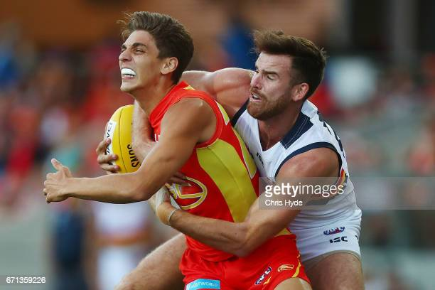 Sean Lemmens of the Suns is tackled by Charlie Cameron of the Crows during the round five AFL match between the Gold Coast Suns and the Adelaide...