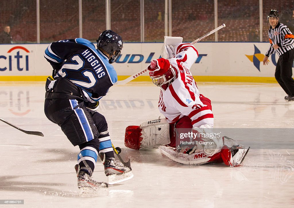 Sean Maguire #31 of the Boston University Terriers makes a save against Stu Higgins #22 of the Maine Black Bears during NCAA hockey action in the 'Citi Frozen Fenway 2014' at Fenway Park on January 11, 2014 in Boston, Massachusetts.