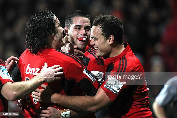 Sean Maitland of the Crusaders is hugged by team mates Zac Guildford and Israel Dagg after scoring a try during the round 18 Super Rugby match...