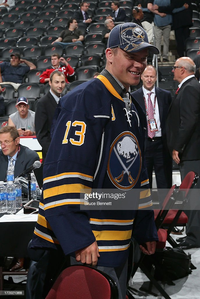 Sean Malone drafted overall in the sixth round by the Buffalo Sabres visits the Sabres organization's draft table during the 2013 NHL Draft at the...