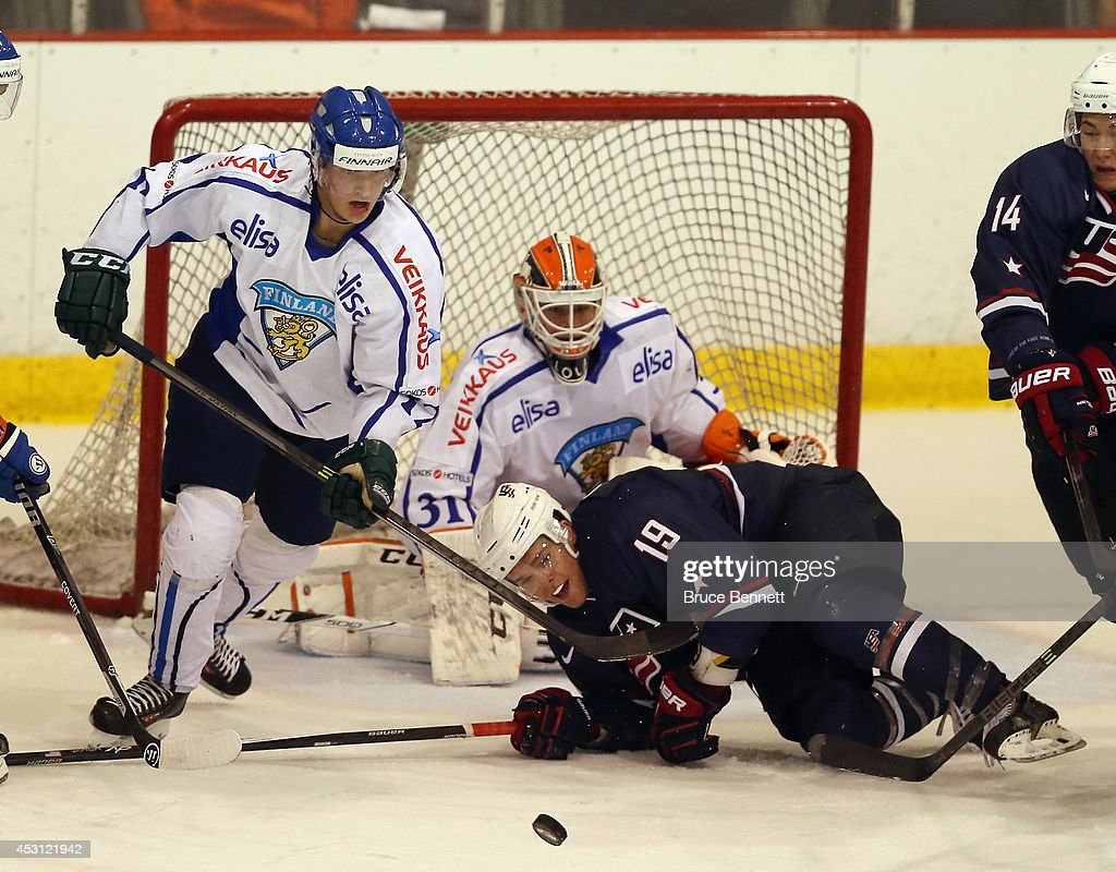 Sean Malone of USA Blue is dumped in front of the net during the game against Team Finland during the 2014 USA Hockey Junior Evaluation Camp at the...