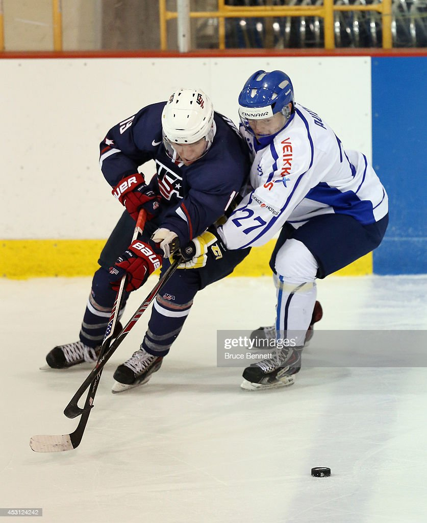 Sean Malone of USA Blue moves the puck around Erik Autio of Team Finland during the 2014 USA Hockey Junior Evaluation Camp at the Lake Placid Olympic...