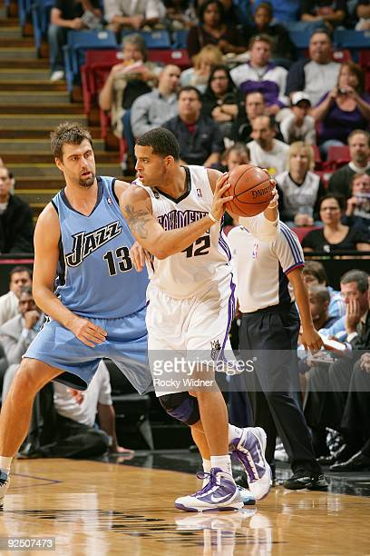 Sean May of the Sacramento Kings drives the ball against Mehmet Okur of the Utah Jazz during the preseason game on October 23 2009 at Arco Arena in...