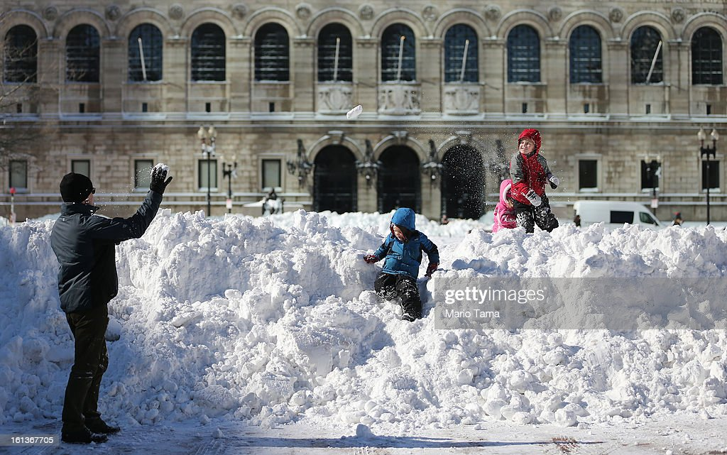 Sean McCullough (L) plays with his children (L to R) Dean, Annie and Will in Copley Square following a powerful blizzard on February 10, 2013 in Boston, Massachusetts. The storm dumped more than two feet of snow in parts of New England and more than 200,000 Massachusetts customers remain without power.