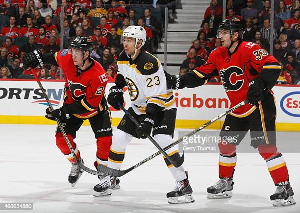 Sean Monahan and Raphael Diaz of the Calgary Flames battle against Chris Kelly of the Boston Bruins at Scotiabank Saddledome on February 16 2015 in...