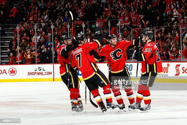 Sean Monahan celebrates a shootout goal with Matt Stajan and teammates of the Calgary Flames against the Dallas Stars during an NHL game at...