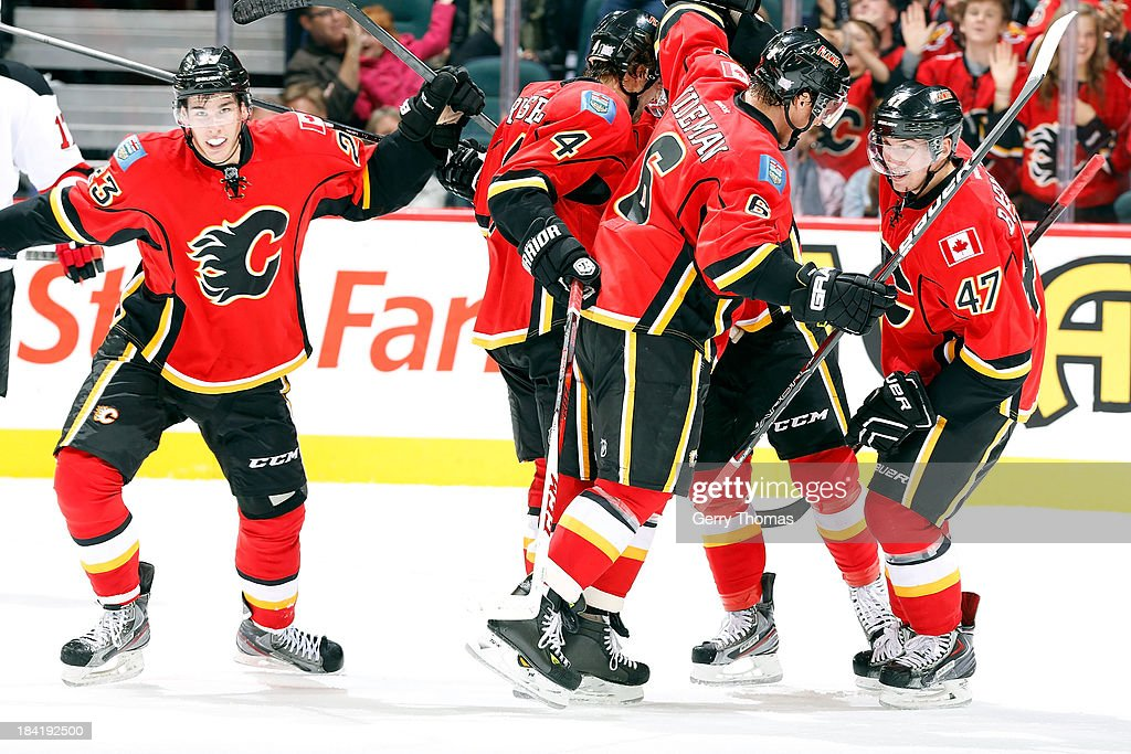 Sean Monahan #23, Kris Russell #4, Dennis Wideman #6 and Sven Baertschi #47 of the Calgary Flames celebrate a goal against the New Jersey Devils at Scotiabank Saddledome on October 11, 2013 in Calgary, Alberta, Canada.