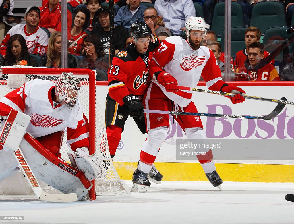 Sean Monahan of the Calgary Flames battles for the puck against Kyle Quincey of the Detroit Red Wings at Scotiabank Saddledome on October 23 2015 in...