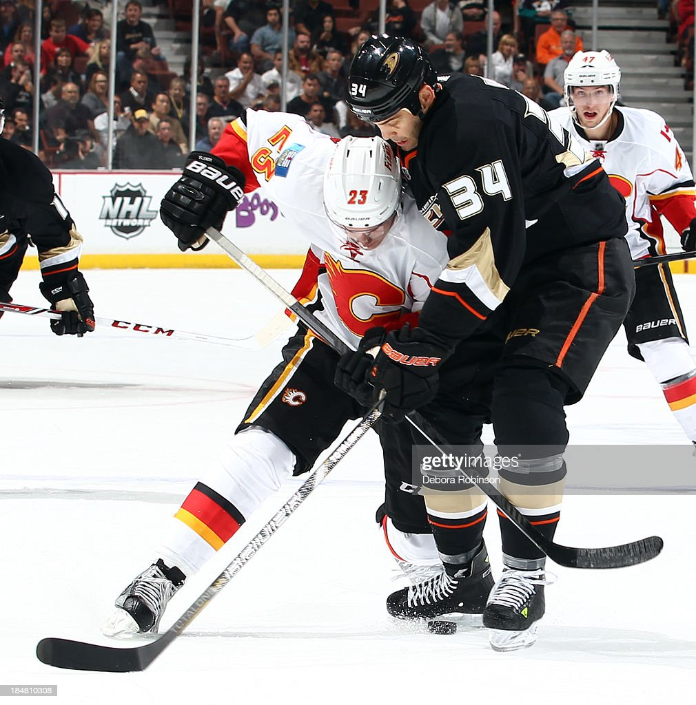 Sean Monahan #23 of the Calgary Flames battles for the puck against Daniel Winnik #34 of the Anaheim Ducks on October 16, 2013 at Honda Center in Anaheim, California.