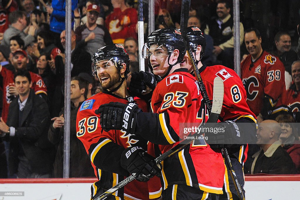 Sean Monahan #23 (C) of the Calgary Flames celebrates along with teammates <a gi-track='captionPersonalityLinkClicked' href=/galleries/search?phrase=T.J.+Galiardi&family=editorial&specificpeople=4324979 ng-click='$event.stopPropagation()'>T.J. Galiardi</a> #39 (L) and <a gi-track='captionPersonalityLinkClicked' href=/galleries/search?phrase=Joe+Colborne&family=editorial&specificpeople=5370968 ng-click='$event.stopPropagation()'>Joe Colborne</a> #8 (R) after scoring against Alex Stalock #32 (not pictured) of the San Jose Sharks during an NHL game at Scotiabank Saddledome on January 30, 2014 in Calgary, Alberta, Canada. The Flames defeated the Sharks 4-1.