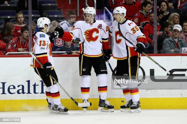 Sean Monahan of the Calgary Flames celebrates scoring a first period goal with teammates Johnny Gaudreau and Alex Chiasson against the Washington...