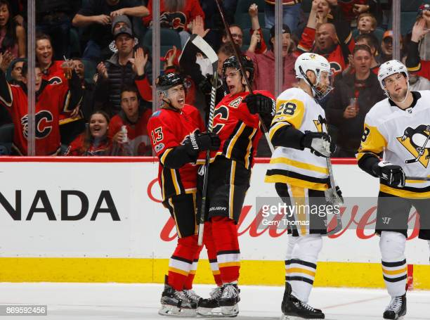 Sean Monahan of the Calgary Flames celebrates with teammate Johnny Gaudreau after a goal against the Pittsburg Penguins at Scotiabank Saddledome on...