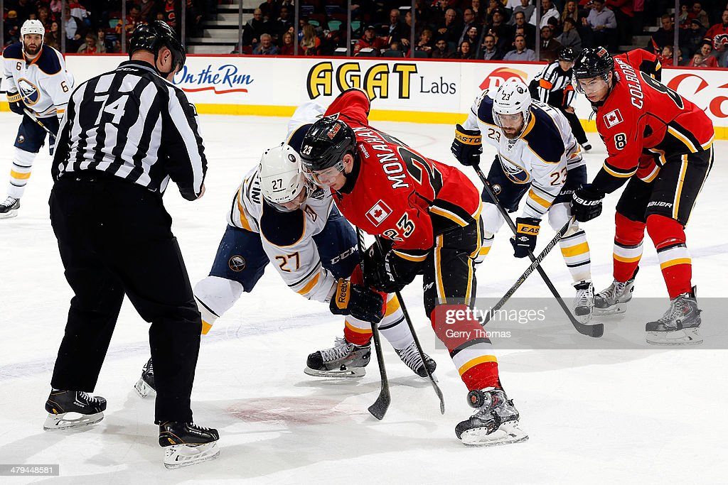 Sean Monahan #23 of the Calgary Flames faces off against <a gi-track='captionPersonalityLinkClicked' href=/galleries/search?phrase=Matt+D%27Agostini&family=editorial&specificpeople=2085764 ng-click='$event.stopPropagation()'>Matt D'Agostini</a> #27 of the Buffalo Sabres at Scotiabank Saddledome on March 18, 2014 in Calgary, Alberta, Canada.