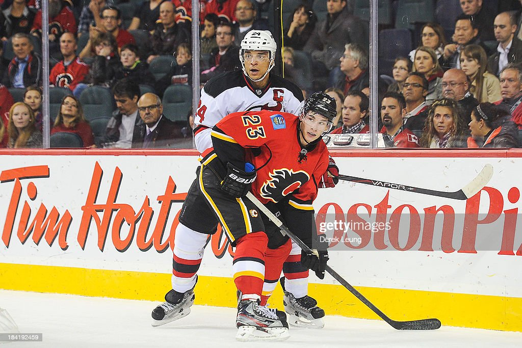 Sean Monahan #23 of the Calgary Flames fights for position against Bryce Salvador #24 of the New Jersey Devils during an NHL game at Scotiabank Saddledome on October 11, 2013 in Calgary, Alberta, Canada. The Calgary Flames defeated the New Jersey Devils 3-2.