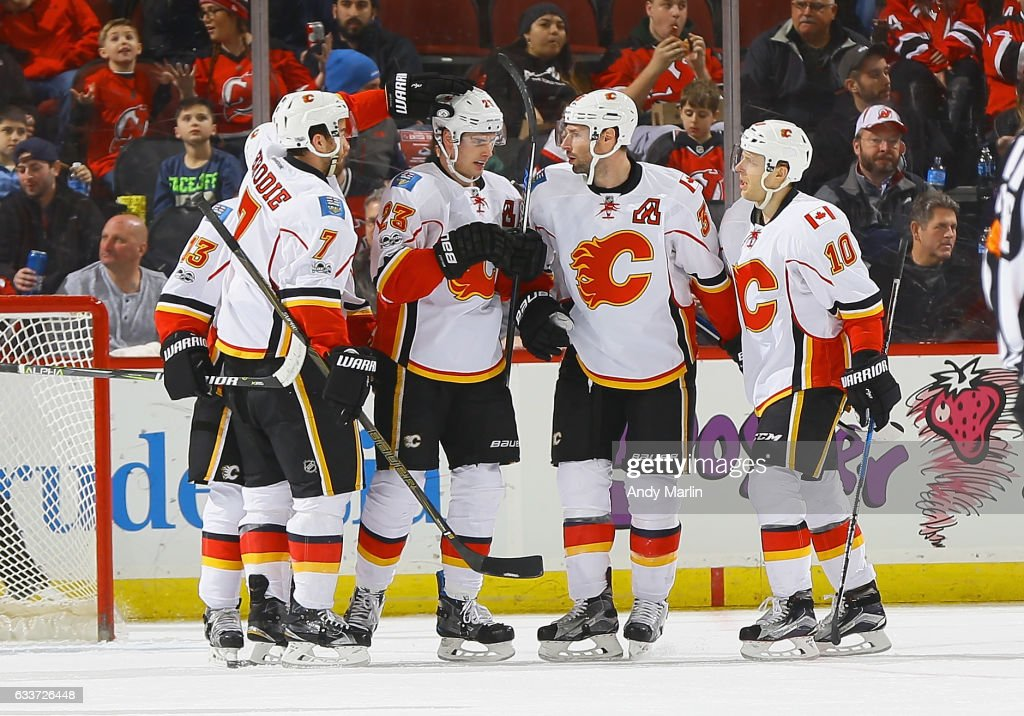 Sean Monahan #23 of the Calgary Flames is congratulated by his teammates after scoring a first-period goal against the New Jersey Devils during the game at Prudential Center on February 3, 2017 in Newark, New Jersey.