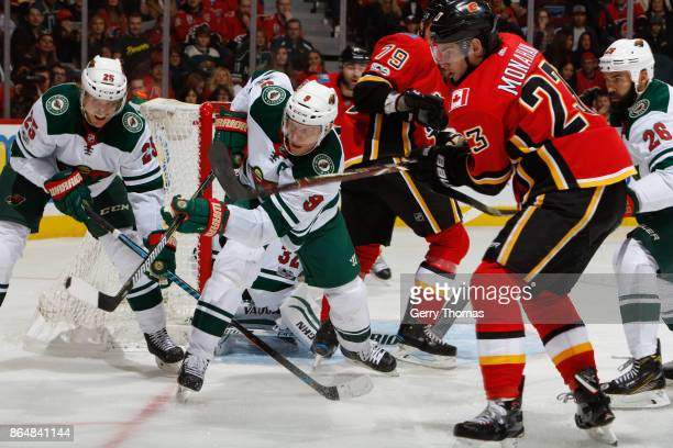 Sean Monahan of the Calgary Flames looks for a pass while Mikko Koivu of the Minnesota Wild tries to deflect in an NHL game against the Minnesota...