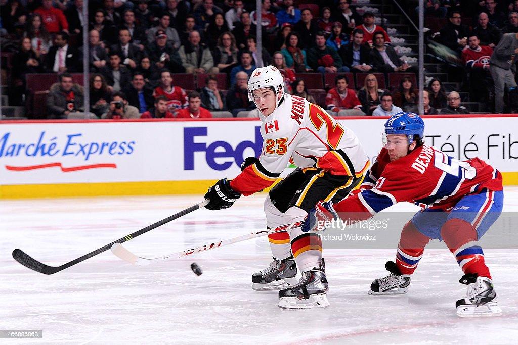 Sean Monahan #23 of the Calgary Flames receives the puck in front of <a gi-track='captionPersonalityLinkClicked' href=/galleries/search?phrase=David+Desharnais&family=editorial&specificpeople=4084305 ng-click='$event.stopPropagation()'>David Desharnais</a> #51 of the Montreal Canadiens during the NHL game at the Bell Centre on February 4, 2014 in Montreal, Quebec, Canada. The Canadiens defeated the Flames 2-0.