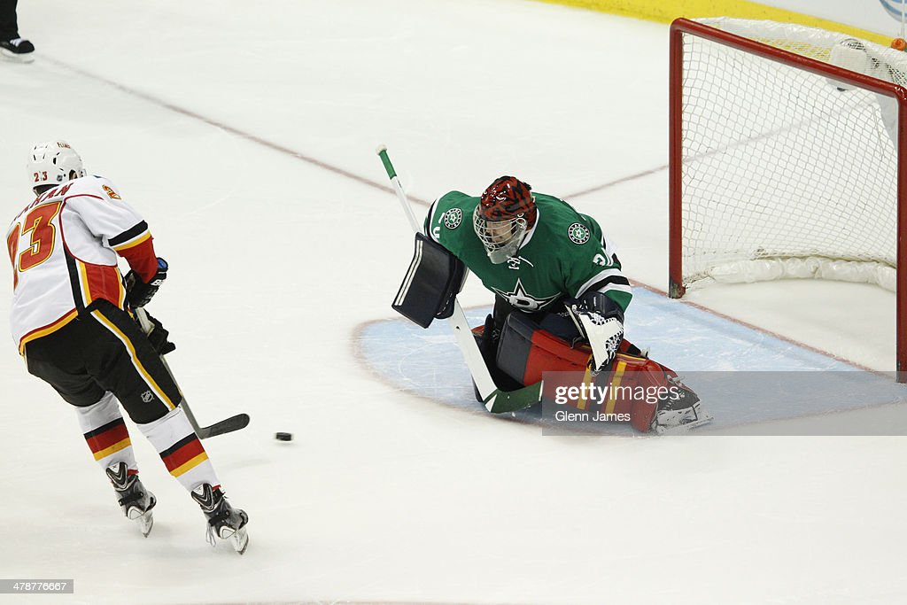 Sean Monahan #23 of the Calgary Flames scores a shootout goal against Tim Thomas #30 of the Dallas Stars at the American Airlines Center on March 14, 2014 in Dallas, Texas.