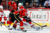 Sean Monahan of the Calgary Flames scores on a backhand against Cam Ward of the Carolina Hurricanes at Scotiabank Saddledome on October 23 2014 in...