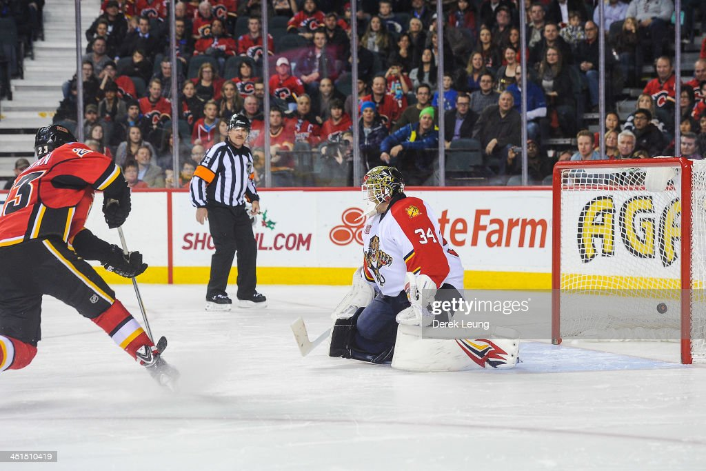 Sean Monahan #23 of the Calgary Flames shoots the puck past Tim Thomas #34 of the Florida Panthers during shootout during an NHL game at Scotiabank Saddledome on November 22, 2013 in Calgary, Alberta, Canada. The Flames defeated the Panthers 4-3 in shootout.