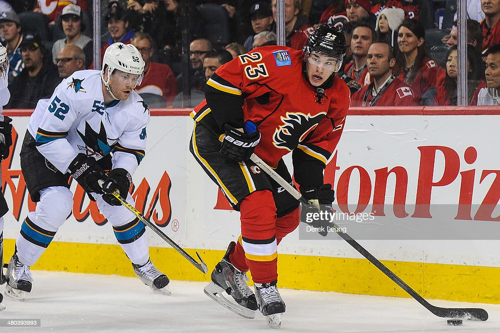 Sean Monahan #23 of the Calgary Flames skates with the puck past Matt Irwin #52 of the San Jose Sharks during an NHL game at Scotiabank Saddledome on March 24, 2014 in Calgary, Alberta, Canada. The Flames defeated the Sharks 2-1 in shootout.