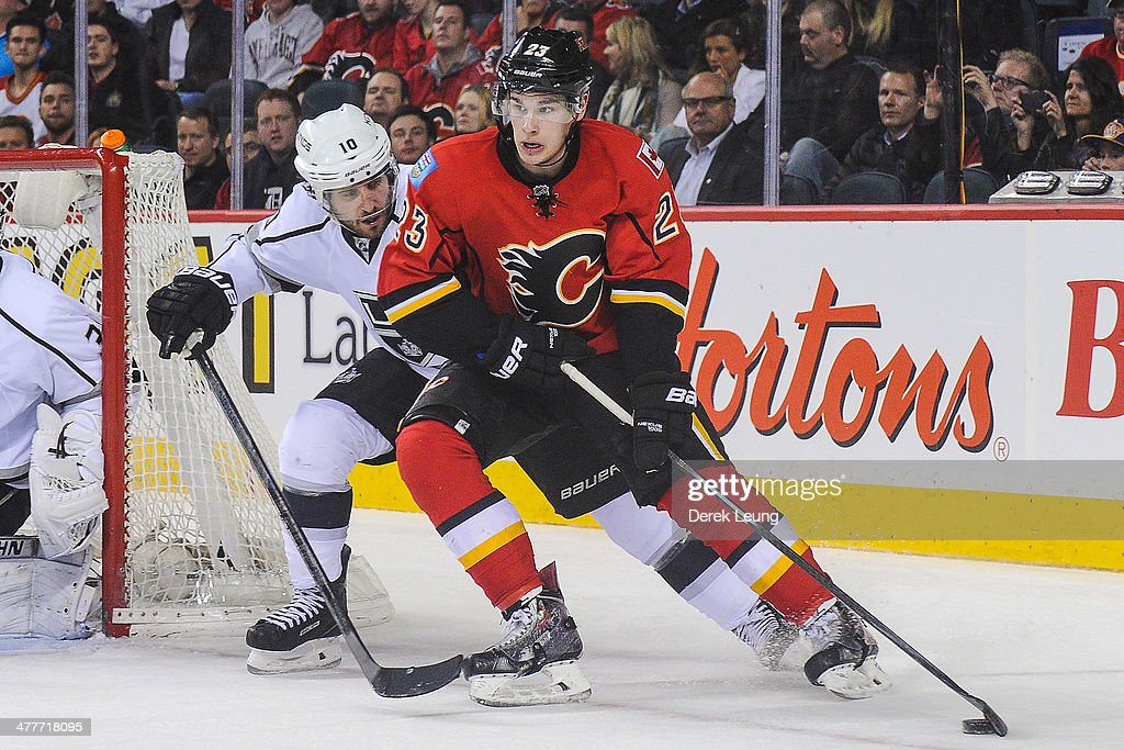 Sean Monahan #23 of the Calgary Flames skates with the puck past Mike Richards #10 of the Los Angeles Kings during an NHL game at Scotiabank Saddledome on March 10, 2014 in Calgary, Alberta, Canada. The Kings defeated the Flames 3-2.