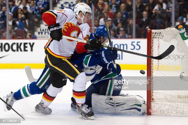 Sean Monahan of the Calgary Flames tries to knock the puck into the net while battling with Chris Tanev of the Vancouver Canucks during the third...