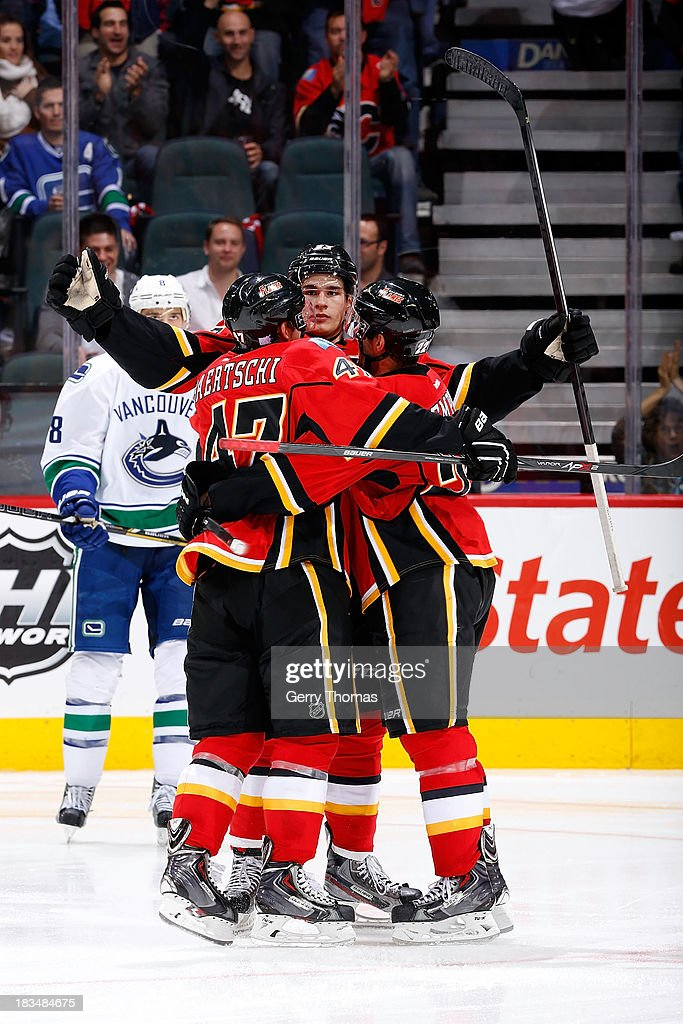 Sean Monahan #23, <a gi-track='captionPersonalityLinkClicked' href=/galleries/search?phrase=Sven+Baertschi&family=editorial&specificpeople=7832299 ng-click='$event.stopPropagation()'>Sven Baertschi</a> #47 and <a gi-track='captionPersonalityLinkClicked' href=/galleries/search?phrase=Lee+Stempniak&family=editorial&specificpeople=575240 ng-click='$event.stopPropagation()'>Lee Stempniak</a> #22 of the Calgary Flames celebrate a goal against the Vancouver Canucks at Scotiabank Saddledome on October 6, 2013 in Calgary, Alberta, Canada.