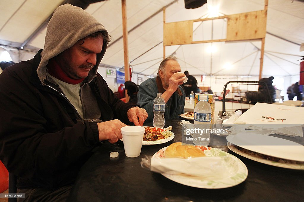 Sean Nolan (L) and his father Stretch Nolan eat a free meal in a warming tent in the hard hit Rockaway neighborhood on December 7, 2012 in the Queens borough of New York City. The Nolan's home flooded and they only have power in two rooms currently. Rockaway was slammed by Superstorm Sandy with many homes severely damaged from flooding.