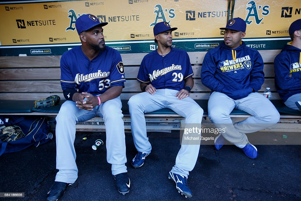 Sean Nolin and Yadiel Rivera of the Milwaukee Brewers sit in the dugout prior to the game against the Oakland Athletics at the Oakland Coliseum on...