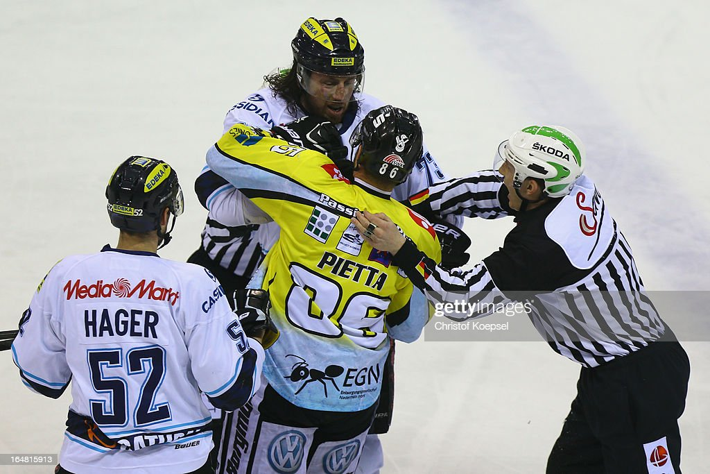 Sean O'Connor of ERC Ingolstadt (2nd L) and Daniel Pietta of Krefeld Pinguine (3rd L) fight against each other during the fifth DEL Play-Off-match between Krefeld Pinguine and ERC Ingolstadt at Koenigspalast on March 28, 2013 in Wuppertal, Germany.