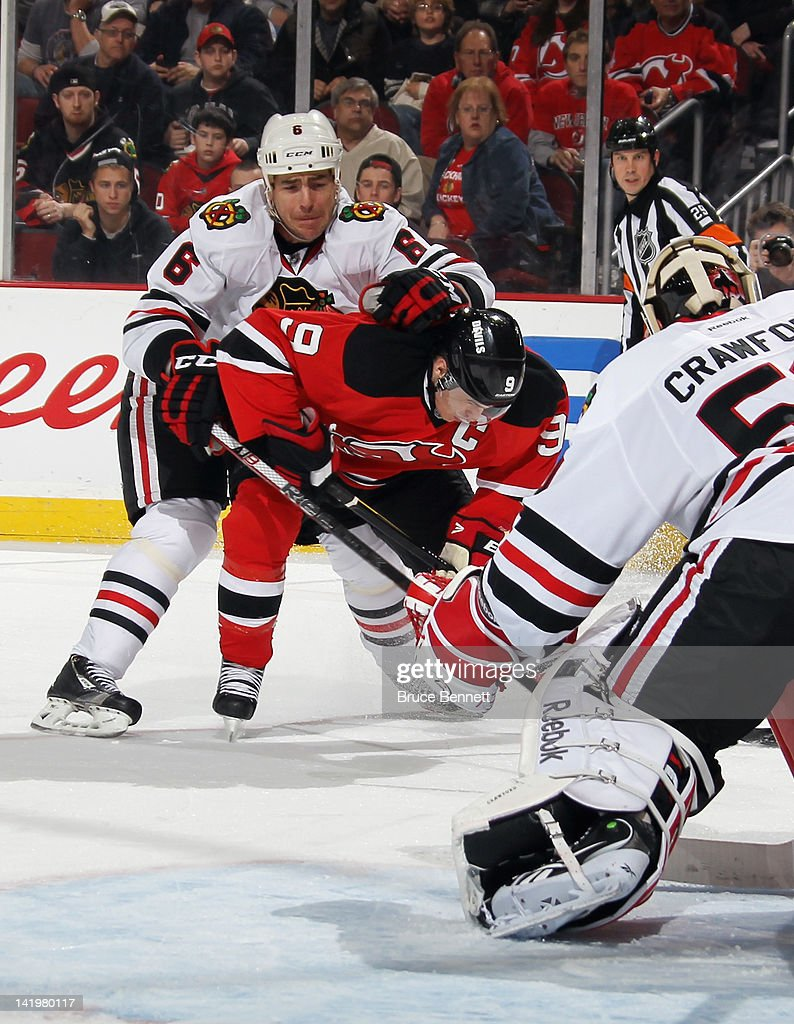 Sean O'Donnell #6 of the Chicago Blackhawks takes a holding penalty on Zach Parise #9 of the New Jersey Devils at the Prudential Center on March 27, 2012 in Newark, New Jersey. The Devils defeated the Blackhawks 2-1 in the shootout.