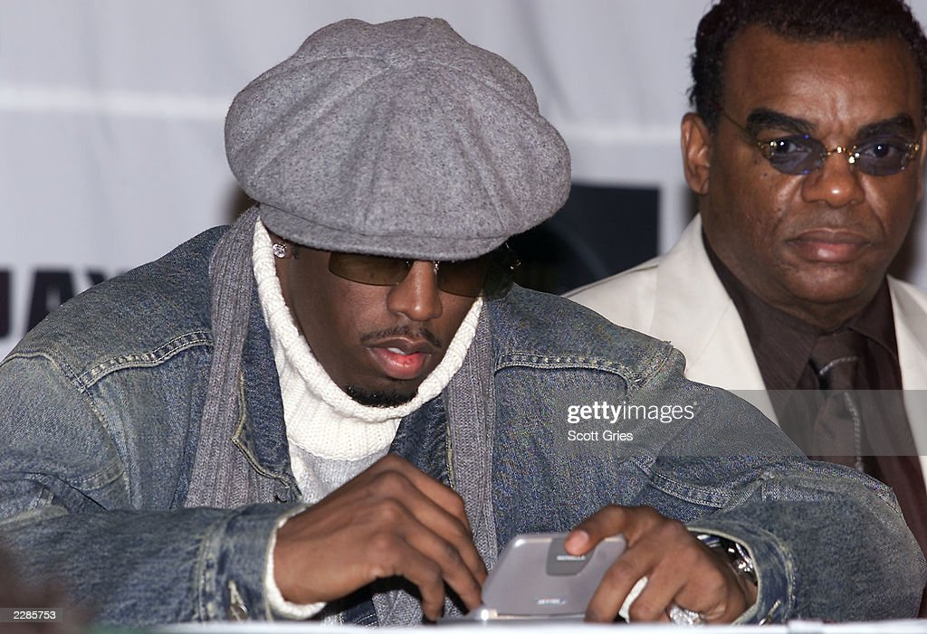 Sean 'P Diddy' Combs on his twoway pager with Ronald Isley in the background during a press conference to announce the release of a new collaborative...