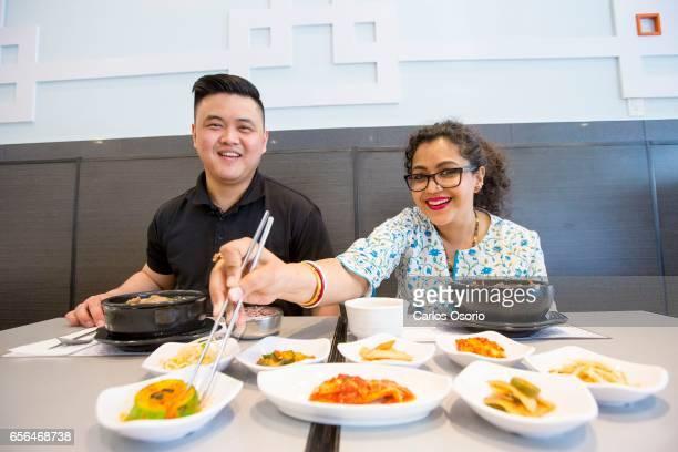 TORONTO ON MAY 11 Sean Park manager at Cho Sun Ok Korean restaurant teaches Aparita Bhandari how to eat banchan on May 11 2016 The pilot for Aparita...